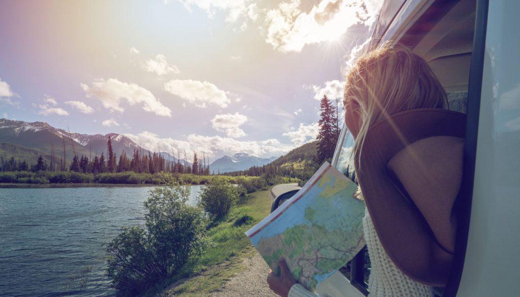 Jeune femme qui lis une carte dans un 4x4 au bord d'un lac, l'été au Canada.
