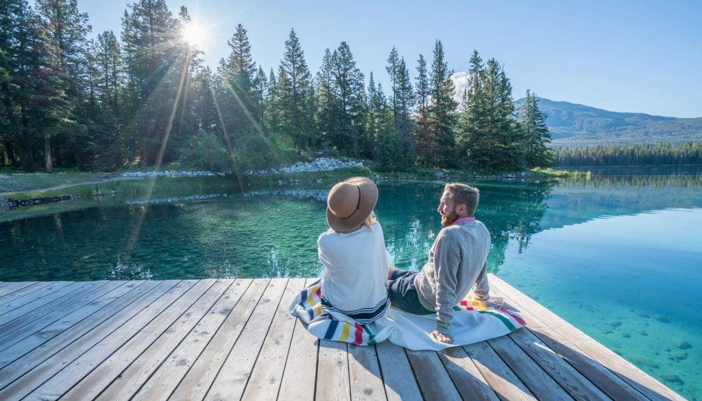 Couple profitant du soleil, au printemps et au bord d'un lac canadien